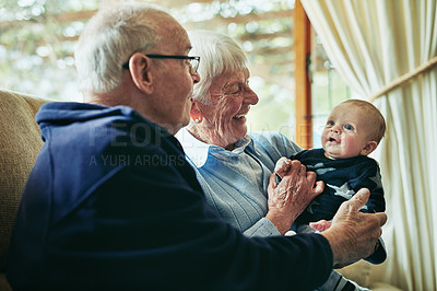 Buy stock photo Shot of grandparents bonding with their little grandson at home