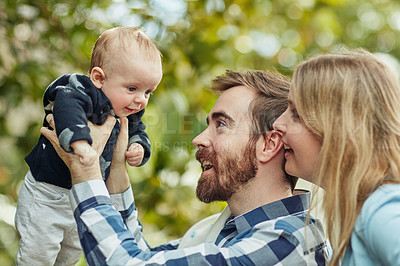Buy stock photo Shot of a mother and a father bonding with their baby boy outdoors