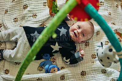 Buy stock photo Shot of an adorable baby boy lying on a play mat at home