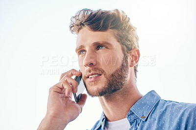 Buy stock photo Shot of a confident young man talking on his cellphone outside during the day