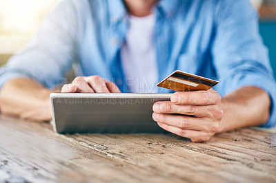 Buy stock photo Shot of an unrecognizable man doing online shopping on his digital tablet and holding his credit card while being seated at a table
