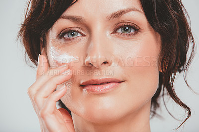 Buy stock photo Studio shot of an attractive woman applying moisturizer to her face against a gray background