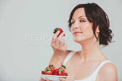 Buy stock photo Shot of a beautiful woman eating strawberries against a grey background
