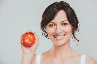 Buy stock photo Studio shot of an attractive woman posing with a tomato against a gray background
