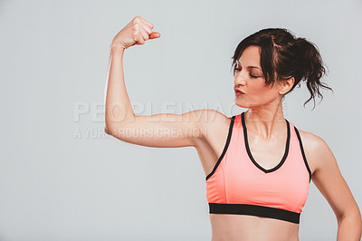 Buy stock photo Studio shot of a sporty young woman flexing her muscles against a grey background