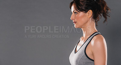 Buy stock photo Studio shot of a sporty young woman posing against a grey background