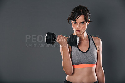 Buy stock photo Studio portrait of a sporty young woman lifting weights against a grey background