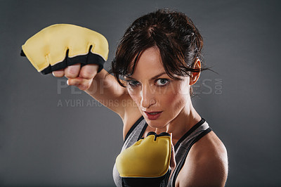 Buy stock photo Studio portrait of a sporty young woman wearing boxing gloves against a grey background