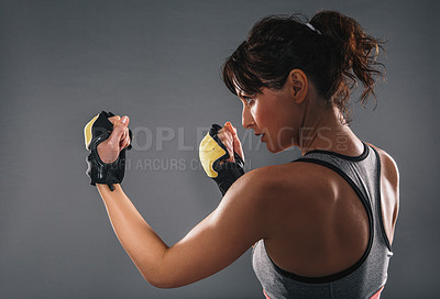 Buy stock photo Studio shot of a sporty young woman wearing boxing gloves against a grey background