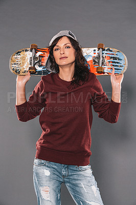 Buy stock photo Studio portrait of an attractive and trendy woman carrying a skateboard against a gray background