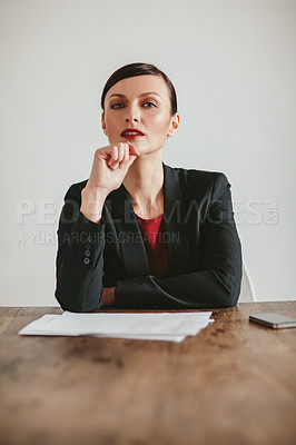 Buy stock photo Portrait of a confident young businesswoman sitting at a table with paperwork against a grey background