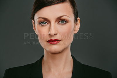 Buy stock photo Studio portrait of a confident young businesswoman against a dark background