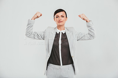 Buy stock photo Studio portrait of an attractive and confident businesswoman flexing her muscles against a gray background