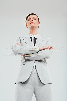 Buy stock photo Studio portrait of an attractive and confident businesswoman folding her arms against a gray background