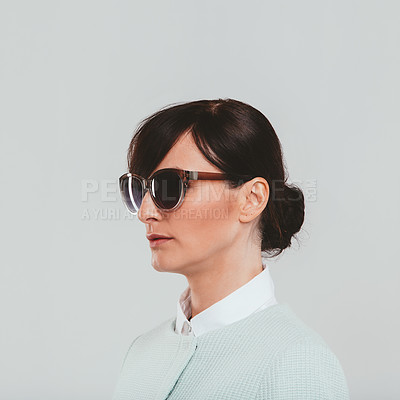 Buy stock photo Studio shot of an attractive woman wearing sunglasses and a preppy outfit against a gray background