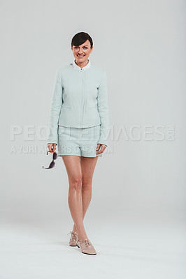 Buy stock photo Studio portrait of an attractive woman wearing a preppy outfit against a gray background