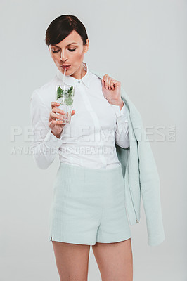 Buy stock photo Studio shot of an attractive woman wearing a preppy outfit and drinking a beverage against a gray background