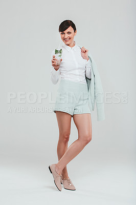 Buy stock photo Studio portrait of an attractive woman wearing a preppy outfit and drinking a beverage against a gray background