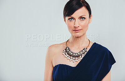 Buy stock photo Studio portrait of an attractive woman wearing an elegant evening gown against a gray background