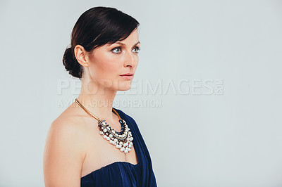 Buy stock photo Studio shot of an attractive woman wearing an elegant evening gown against a gray background