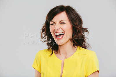 Buy stock photo Studio shot of an attractive and expressive woman making posing against a gray background