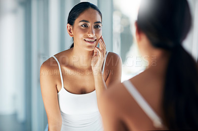 Buy stock photo Cropped shot of an attractive young woman inspecting her skin in front of the bathroom mirror