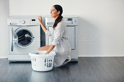 Buy stock photo Shot of a young attractive woman doing her laundry at home