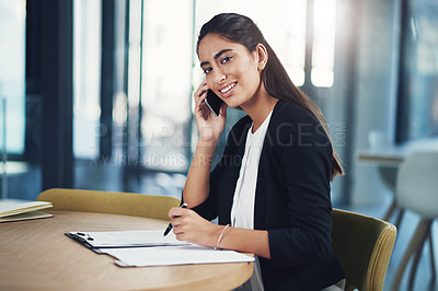Buy stock photo Portrait of a young businessman talking on a cellphone in an office