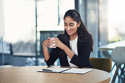 Buy stock photo Shot of a young businesswoman drinking coffee while working in an office