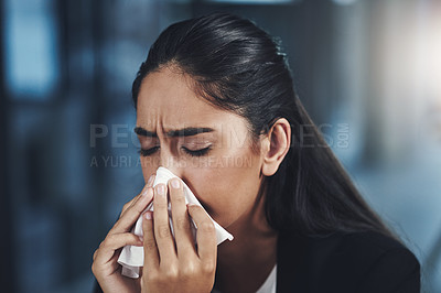 Buy stock photo Shot of a young businesswoman blowing her nose in an office
