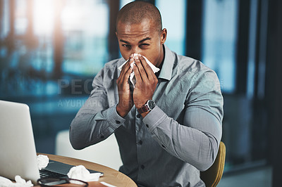 Buy stock photo Portrait of a young businessman blowing his nose while working in an office