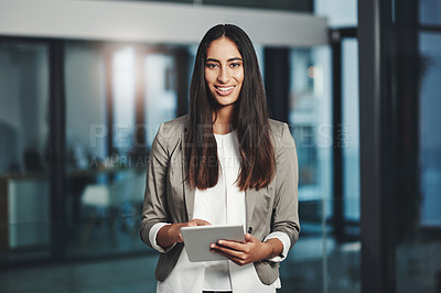 Buy stock photo Portrait of a young businesswoman working on a digital tablet in an office