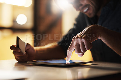 Buy stock photo Cropped shot of an unrecognizable male designer using his digital tablet to shop online while working in the office