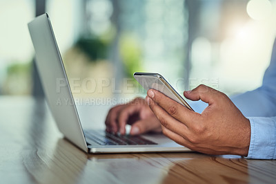 Buy stock photo Cropped shot of a businessman using a mobile phone and laptop at his desk in a modern office