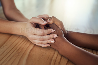 Buy stock photo Cropped shot of two women compassionately holding hands at a table