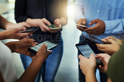 Buy stock photo Cropped shot of a group of businesspeople using their phones in synchronicity