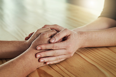 Buy stock photo Cropped shot of a man and woman compassionately holding hands at a table