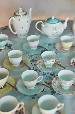 Buy stock photo Shot of tea pots and tea cups laid out on a table at a tea party inside