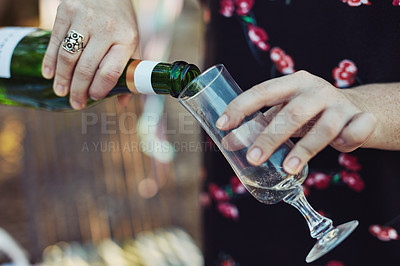 Buy stock photo Closeup shot of an unrecognizable woman pouring champagne into a glass at a tea party outside