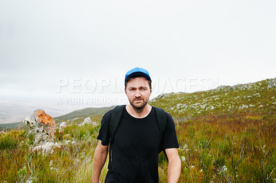 Buy stock photo Portrait of a young man hiking through the mountains