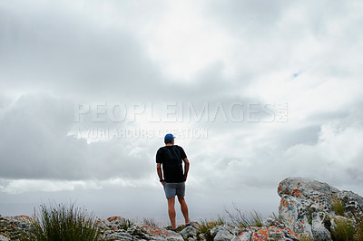 Buy stock photo Rearview shot of a young man admiring the scenic view while out on a hike
