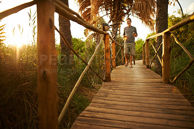 Buy stock photo Shot of a young man walking on a bridge at a resort in nature