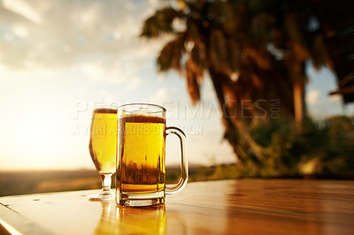Buy stock photo Shot of beer in two glasses on a table outdoors with no people