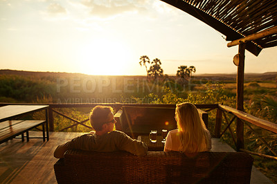 Buy stock photo Rearview shot of an unrecognizable couple having a drink outside at a resort in nature