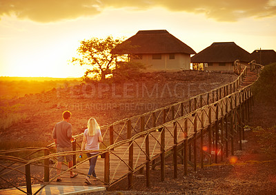 Buy stock photo Shot of a young married couple walking on a bridge at a resort in nature