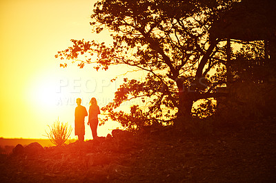 Buy stock photo Silhouette shot of an unrecognizable couple having a drink and enjoying the sunset at a resort in nature
