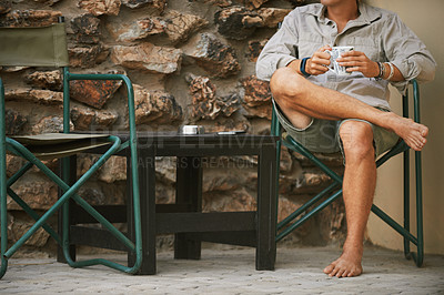 Buy stock photo Cropped shot of an unrecognizable man drinking a cup of coffee at a resort in nature