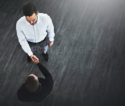Buy stock photo High angle shot of two businessmen shaking hands in an office