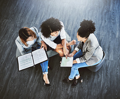 Buy stock photo High angle shot of a group of businesswomen having a discussion in an office