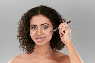 Buy stock photo Studio shot of a beautiful young woman applying foundation with a make up brush against a gray background